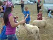 Hopper and Esme Burson hand feed farm animals.