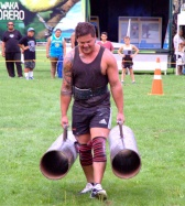 Jason George does the farmer's walk with 2 x 100kg weights.